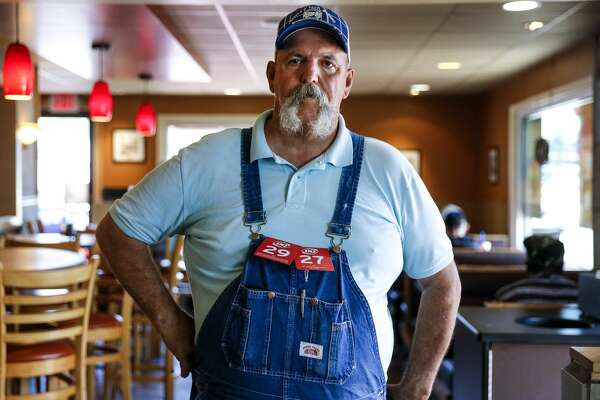 Sidney LaVasseur hangs his order tags off his overalls as he waits for his food at the Dairy Queen in Henderson.