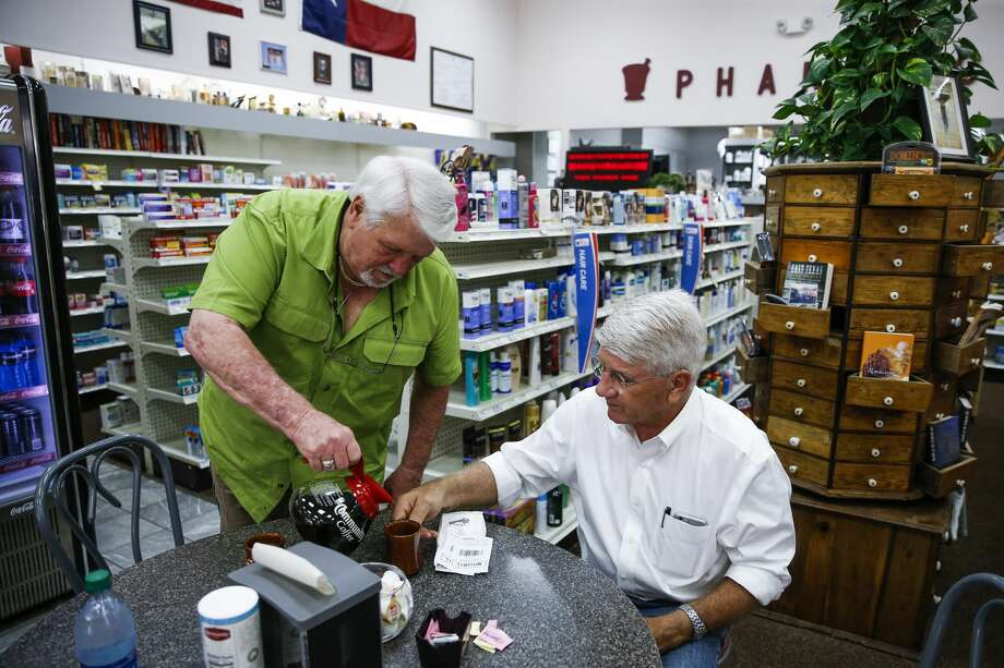 Ron Cook, left, fills his cup before topping off the coffee of San Augustine County district judge Charles Mitchell, right, at the soda fountain inside the San Augustine Drug Co. in San Augustine. Photo: Michael Ciaglo