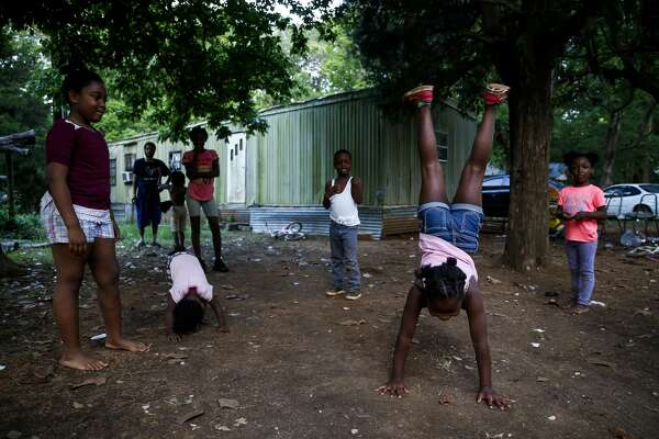 Lyrica Clifton, 9, second from right, shows off her handstand to her cousins in San Augustine.