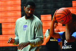 Former Edwardsville and Western Illinois star Garret Covington, left, gives shooting advice to a camper during an EHS boys' basketball camp.