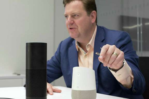 In this June 14, 2018, photo, Gareth Gaston, Executive Vice President and Head of Omnichannel Banking at US Bank, discusses voice assistant banking with an Amazon Echo, left, and a Google Home, right, in New York. Big banks and financial companies have started to offer banking through virtual assistants, Amazons Alexa, Apples Siri, and Googles Assistant, in a way that will allow customers to check their balances, pay bills and, in the near future, send money just with their voice. Regional banking giant U.S. Bank is the first bank to be on all three services, Alexa, Siri and Assistant.
