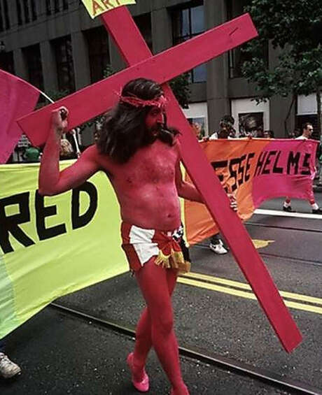 "Gilbert Baker as ""Pink Jesus"" at a Gay Pride celebration in 1990. He spray-painted himself pink and was a ""Martyr for Art"" to protest U.S. Senator Jesse Helms' efforts to defund the National Endowment for the Arts."