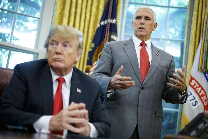 """US Vice President Mike Pence speaks as US President Donald Trump looks on before signing an executive order on immigration in the Oval Office of the White House on June 20, 2018 in Washington, DC. US President Donald Trump on Wednesday signed an executive order aimed at putting an end to the controversial separation of migrant families at the border, reversing a harsh practice that had earned international scorn.""""It's about keeping families together,"""" Trump said at the signing ceremony. """"I did not like the sight of families being separated,"""" he added.  / AFP PHOTO / Mandel NganMANDEL NGAN/AFP/Getty Images"""