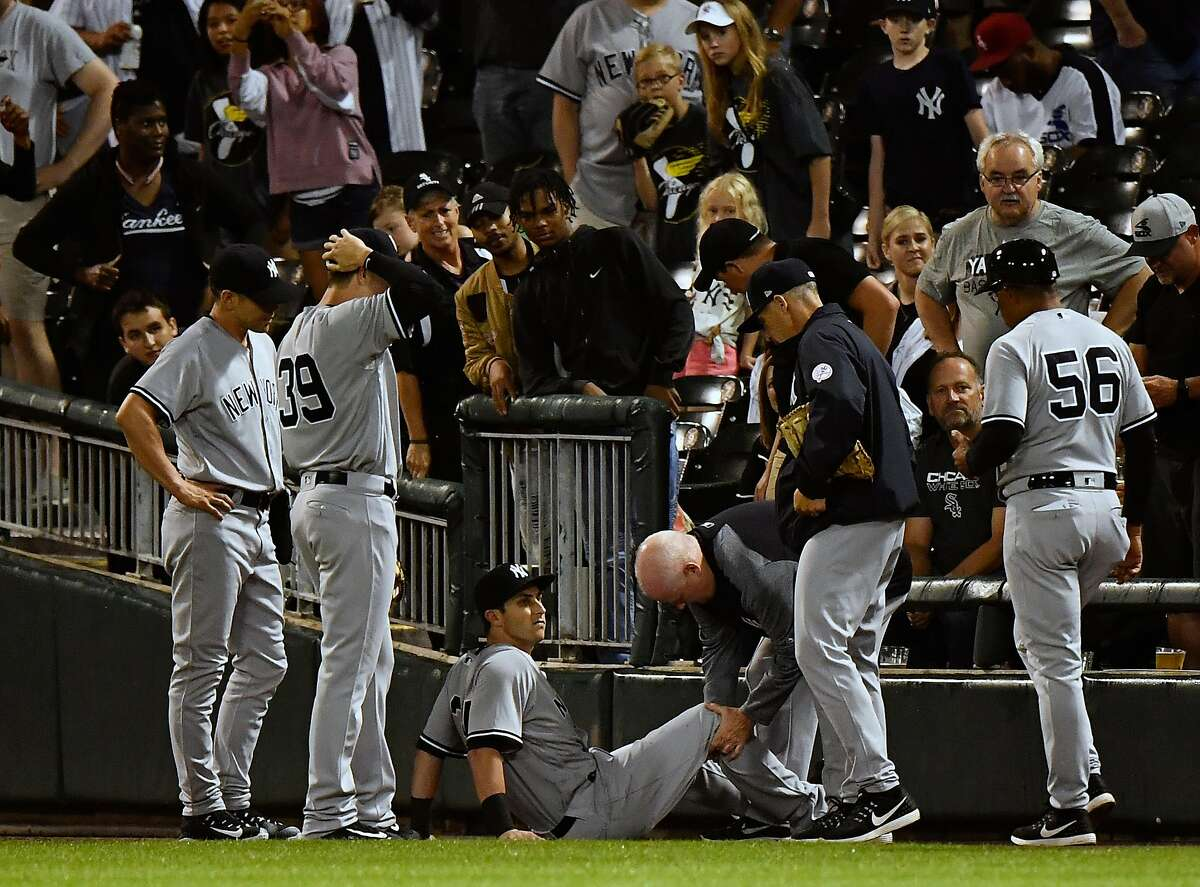 CHICAGO, IL - JUNE 29: New York Yankees right fielder Dustin Fowler (34) is evaluated by medical staff after injuring his leg chasing down a foul ball during the game between the New York Yankees and the Chicago White Sox on June 29, 2017 at Guaranteed Rate Field in Chicago, Illinois. (Photo by Quinn Harris/Icon Sportswire via Getty Images)