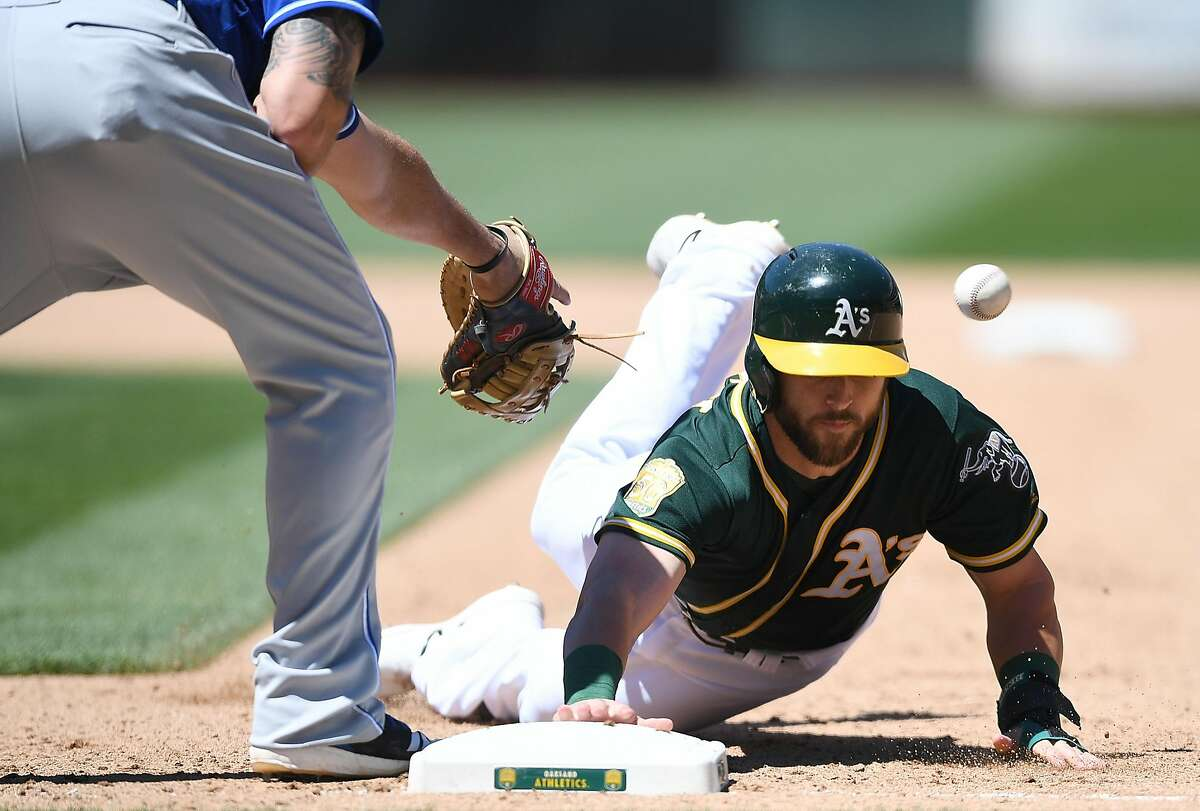 OAKLAND, CA - JUNE 10: Dustin Fowler #11 of the Oakland Athletics dives back into first base safe as the ball gets thown past Mike Moustakas #8 of the Kansas City Royals in the bottom of the seventh inning at the Oakland Alameda Coliseum on June 10, 2018 in Oakland, California. (Photo by Thearon W. Henderson/Getty Images)