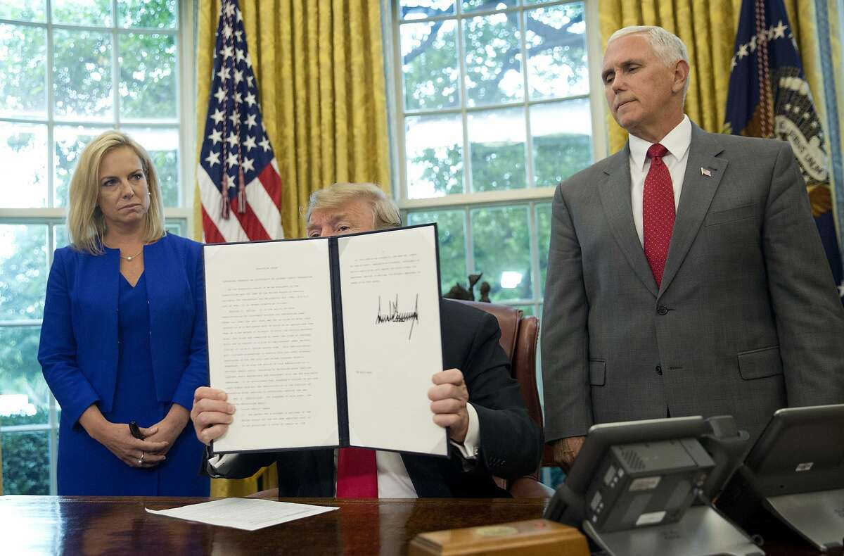 President Donald Trump holds up an executive order he signed to end family separations at the border, during an event in the Oval Office of the White House in Washington, Wednesday, June 20, 2018. Standing behind Trump are Homeland Security Secretary Kirstjen Nielsen, left, and Vice President Mike Pence. (AP Photo/Pablo Martinez Monsivais)