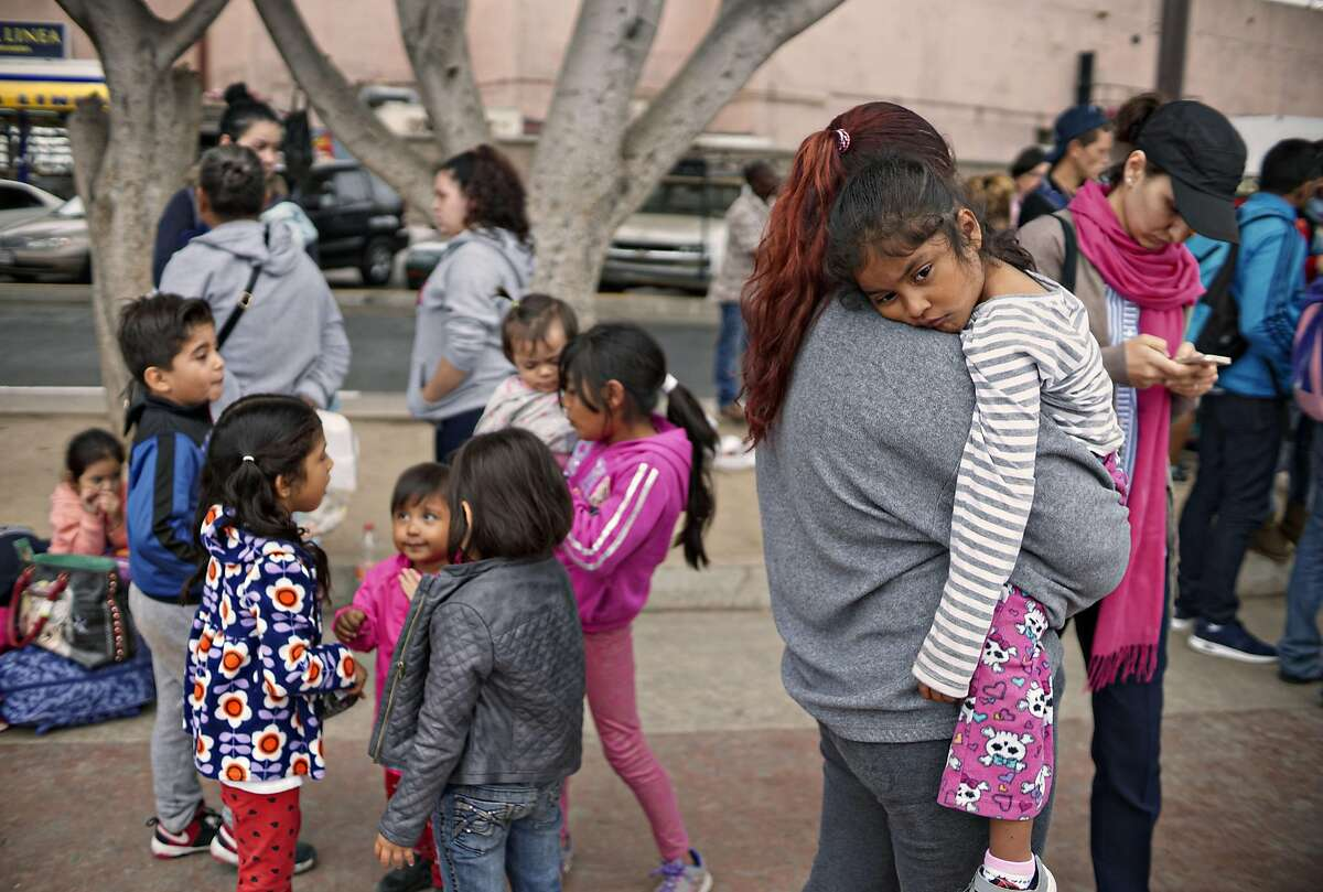 Undocumented migrants wait for asylum hearings outside the port of entry in Tijuana, Mexico, June 20, 2018. President Donald Trump caved to enormous political pressure on Wednesday and signed an executive order that ends the separation of families by indefinitely detaining parents and children together at the border.