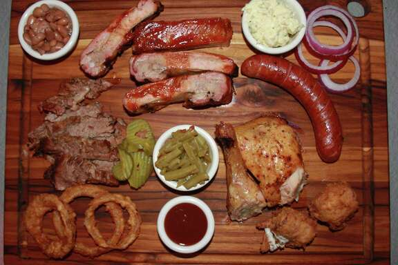The board at Big Lou's Burgers & BBQ includes (from top left) pinto beans, spare ribs, potato salad, sausage, jalapeño poppers, chicken, green beans, onion rings and brisket.