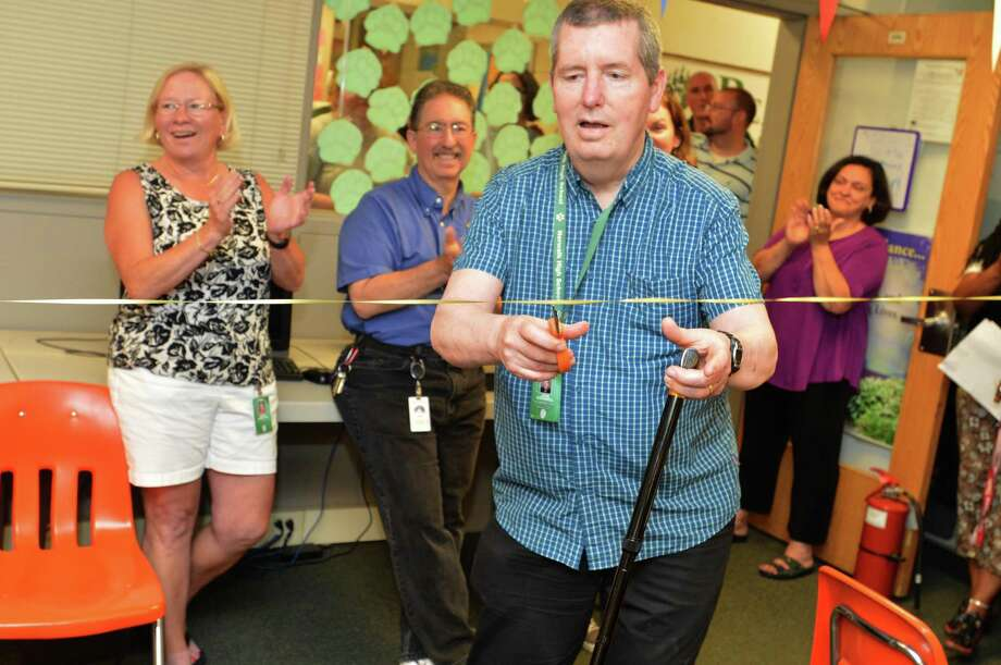 Above, longtime Norwalk High School guidance counselor John O'Donnell cuts a ribbon during a renaming party on Tuesday for the schools College and Career Center, which will now be named after him as he retires this year. Photo: Alex Von Kleydorff / Hearst Connecticut Media / Norwalk Hour