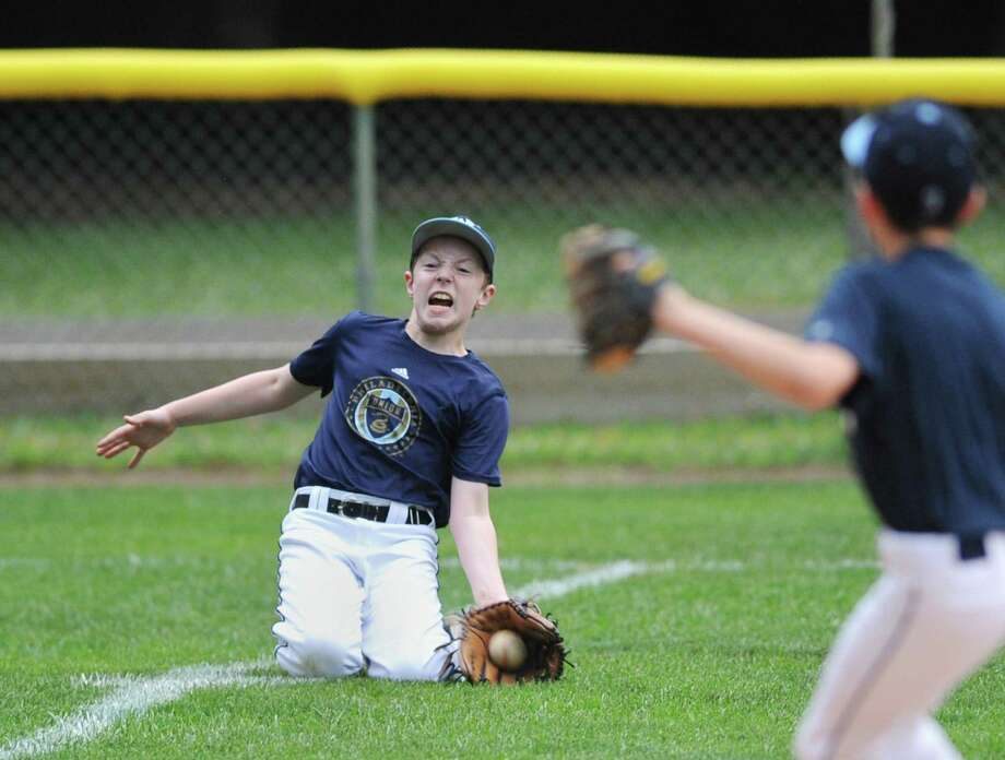 Centerfielder Michael Fischetti makes a sliding catch at the Wilton Little League 12-year-old All-Stars practice at the YMCA in Wilton, Conn. Monday, June 18, 2018. Wilton opens District 1 play on Wednesday, June 27, hosting Stamford American at the Wilton YMCA's Bill Terry Field. Photo: Tyler Sizemore / Hearst Connecticut Media / Greenwich Time