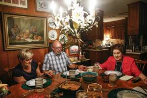 Before digging into the home-cooked meal, Betty Oglesbee, right, holds hands and prays with her son, John Oglesbee, center, and his wife, Sharon Oglesbee.