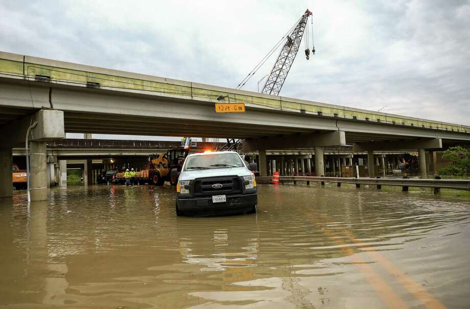 Crews work to move construction equipment off the road that is under the U.S. 59 overpass as the west fork of the San Jacinto River overflowed Thursday, March 29, 2018, in Humble, Texas. ( Godofredo A. Vasquez / Houston Chronicle ) Photo: Godofredo A. Vasquez / Houston Chronicle