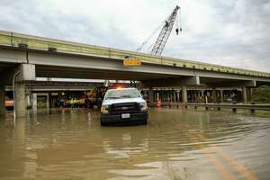 Crews work to move construction equipment off the road that is under the U.S. 59 overpass as the west fork of the San Jacinto River overflowed Thursday, March 29, 2018, in Humble, Texas. ( Godofredo A. Vasquez / Houston Chronicle )