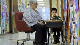 Grace Scalera Manning reads with kindergartner Max Ellenberg, 6, in the hallway at Consolidated School May 10, 2017, in New Fairfield, Connecticut. Such volunteering signals that seniors are redefining their retirements.