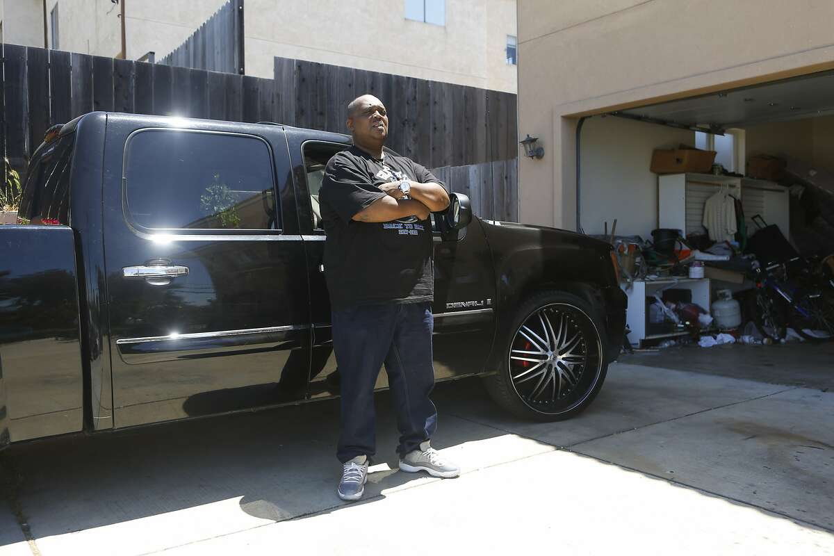 Carlos Smith stands with his GMC Seiara Denali at his home on Tuesday, June 19, 2018 in San Leandro, Calif. His truck was repossessed multiple times by a fraudulent loan company that he paid $8,600 to for a $4,000 loan over the course of four years.