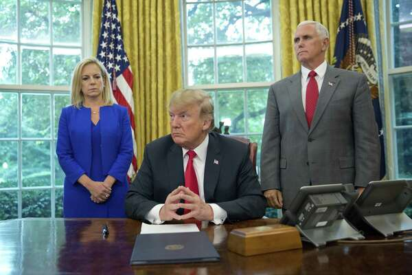 President Trump, center, with Homeland Security Secretary Kirstjen Nielsen, left, and Vice President Mike Pence, before signing an executive order to end family separations, during an event in the Oval Office Wednesday, June 20, 2018.