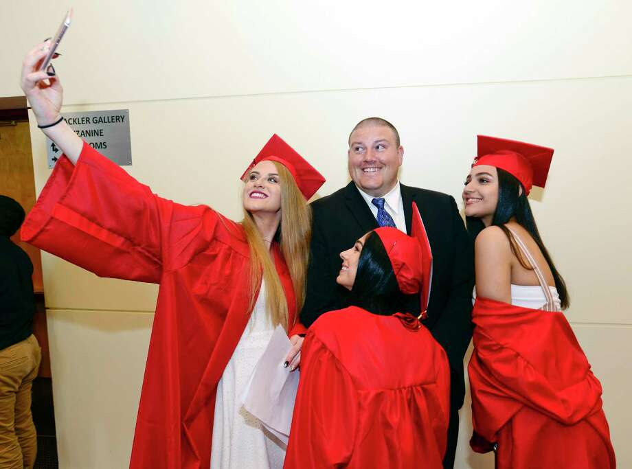 Class President Ella Nilsen takes a selfie with some of her friends and Class Advisor Robert Kucharski prior to J.M. Wright Technical High School Class of 2018 commencement ceremony at The Palace Theatre in Stamford, Conn. on June 20, 2018. This is the first graduation for the school since it reopened in August of 2014. Photo: Matthew Brown, Hearst Connecticut Media / Stamford Advocate