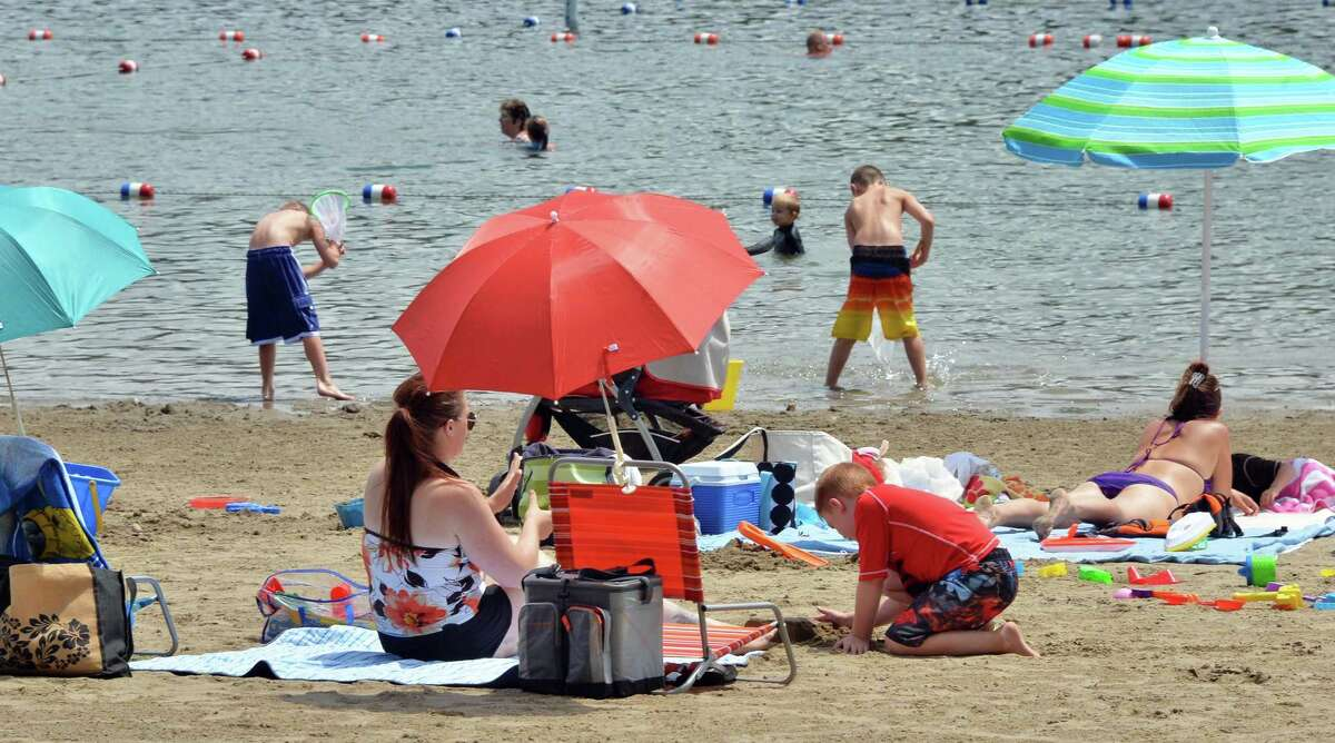File - Beach goers at Moreau Lake State Park on Thursday, July 11, 2013, in Moreau, N.Y. The state Office of Parks, Recreation and Historic Preservation is distributing educational pamphlets about swimmer?s itch at Moreau Lake beach after two families reported skin irritations following a visit to the beach. (John Carl D'Annibale/Times Union archive)