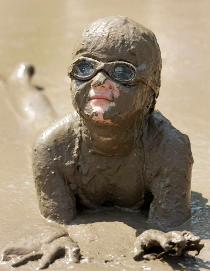 WESTLAND, MI - JULY 6: Hannah Rose Akerley, age 7, of Grosse Point Park, Michigan, gets some relief from the heat by playing in a gigantic lake of mud at the annual Mud Day event July 6, 2010 in Westland, Michigan. The lake was created by mixing approximately 20,000 gallons of water with 200 tons of topsoil. The event, which is sponsored by the Wayne County Parks Department,  draws about 1,000 children each year. (Photo by Bill Pugliano/Getty Images) *** Local Caption *** Hannah Rose Akerley Photo: Bill Pugliano, Getty Images / 2010 Getty Images