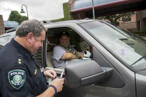 """""""Cut off this hospital band,"""" John Barnes, right, says to Gary Forward as he is released from the hospital on Wednesday, June 20, 2018, in Houston. Barnes credits Forward with saving his life after he was shot in the line of duty during the May 18 shooting at Santa Fe High School."""