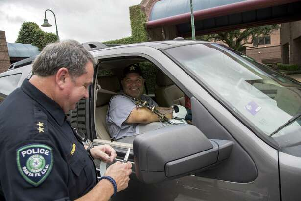 """Cut off this hospital band,"" John Barnes, right, says to Gary Forward as he is released from the hospital on Wednesday, June 20, 2018, in Houston. Barnes credits Forward with saving his life after he was shot in the line of duty during the May 18 shooting at Santa Fe High School."