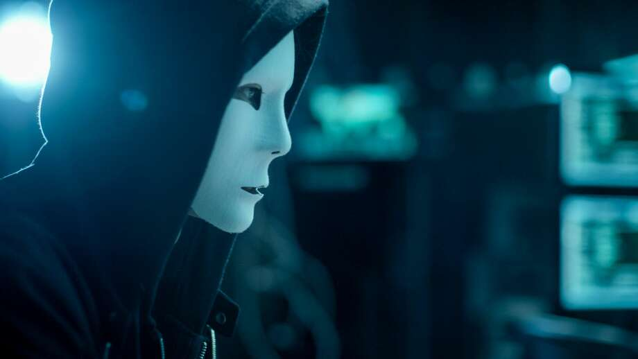 Close-up Shot of Masked Anonymous Hacker Organizes malware Attack on Global Scale. He is in Underground Secret Location Surrounded by Displays and Cables. Photo: Gorodenkoff/Getty Images/iStockphoto