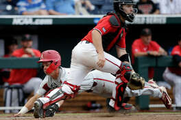 Arkansas' Casey Martin, rear, scores behind Texas Tech catcher Braxton Fulford on a single by Dominic Fletcher in the eighth inning of an NCAA College World Series baseball game in Omaha, Neb., Wednesday, June 20, 2018. Arkansas won 7-4. (AP Photo/Nati Harnik)