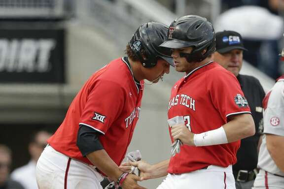 Texas Tech's Michael Davis, right, and Cameron Warren, left, score runs against Arkansas on a single by Cody Farhat in the ninth inning of an NCAA College World Series baseball game in Omaha, Neb., Wednesday, June 20, 2018. Arkansas won 7-4. (AP Photo/Nati Harnik)