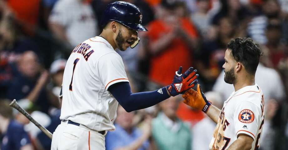 Houston Astros shortstop Carlos Correa (1) and second baseman Jose Altuve high five as they celebrate Altuve's solo home run off of Tampa Bay Rays starting pitcher Nathan Eovaldi during the sixth inning of a major league baseball game at Minute Maid Park on Wednesday, June 20, 2018, in Houston. It was his second home run of the game. ( Brett Coomer / Houston Chronicle ) Photo: Brett Coomer/Houston Chronicle