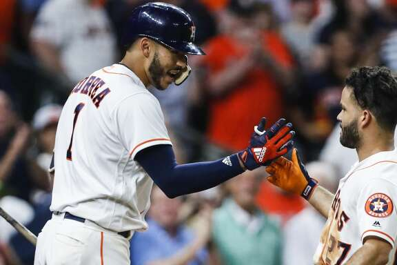 Houston Astros shortstop Carlos Correa (1) and second baseman Jose Altuve high five as they celebrate Altuve's solo home run off of Tampa Bay Rays starting pitcher Nathan Eovaldi during the sixth inning of a major league baseball game at Minute Maid Park on Wednesday, June 20, 2018, in Houston. It was his second home run of the game. ( Brett Coomer / Houston Chronicle )