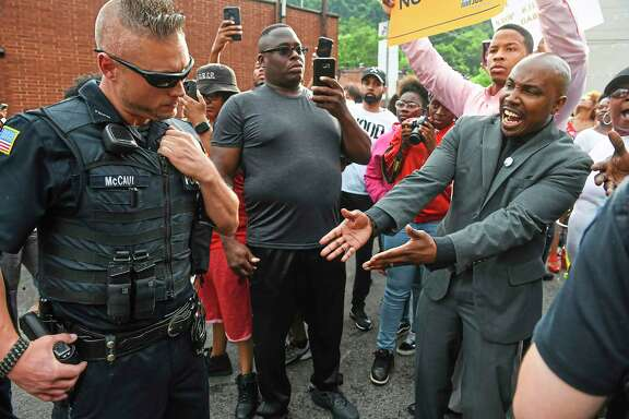 Leonard Hammonds II, of Penn Hills, right, points out that a Turtle Creek Police officer has his had on his weapon during a rally in East Pittsburgh, Pa., on Wednesday, June 20, 2018, at a protest regarding the shooting death of Antwon Rose by an East Pittsburgh Police officer during a traffic stop the night before. (Steve Mellon/Pittsburgh Post-Gazette via AP)