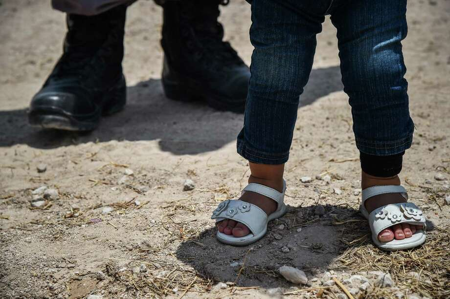 Karina Lopez's 1-year-old daughter stands next to her mother after they were detained by U.S. Border Patrol agents after crossing illegally into the United States on June 29, 2017, in McAllen, Texas.