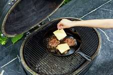 Cook in a cast-iron skillet, even on the grill. You can control the patty better, and the juices don't drip through the grates.