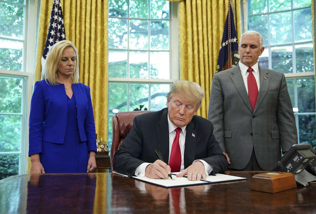 """TOPSHOT - Watched by Homeland Security Secretary Kirstjen Nielsen (L) and Vice President Mike Pence, US President Donald Trump signs an executive order on immigration in the Oval Office of the White House on June 20, 2018 in Washington, DC. US President Donald Trump on Wednesday signed an executive order aimed at putting an end to the controversial separation of migrant families at the border, reversing a harsh practice that had earned international scorn.""""It's about keeping families together,"""" Trump said at the signing ceremony. """"I did not like the sight of families being separated,"""" he added."""