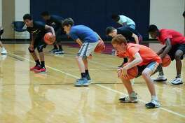 Tristan Hogan, Ryan Guillo and Henry Stadler try to stay focused during a ball handling drill at the Dawson High School summer basketball camp.