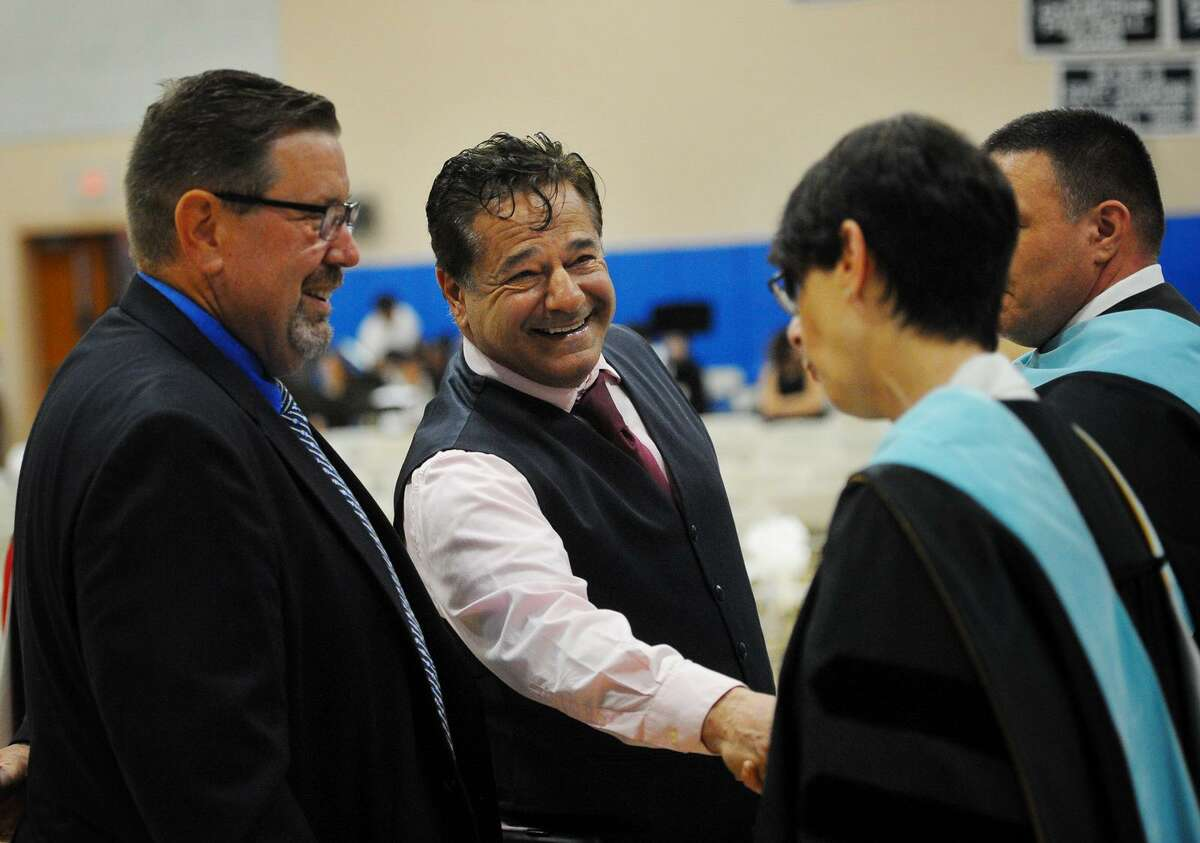 Ansonia Mayor David Cassetti shakes hands with Superintendent of Schools Carol Merlone while Chris Phipps, a Board of Education member and Assistant Supt. of Schools Joseph DiBacco look on during Monday's Ansonia High School Commencement.