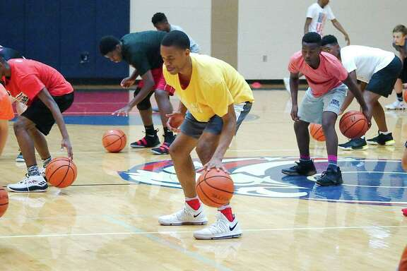 Conlie Christmas joins a host of athletes in a ball handling drill at the Dawson High School summer basketball camp.