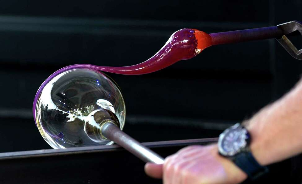 Hot colored glass is applied to another piece of hot glass as a bowl is created during a demonstration on the Corning Museum of Glass GlassBarge on Thursday, June 21, 2018, in Troy, N.Y. (Paul Buckowski/Times Union)