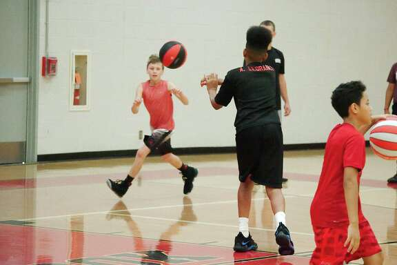 Tristan Lisbany receives a pass from Andrew Llorance in a passing drill at the Clear Brook High School summer basketball camp.
