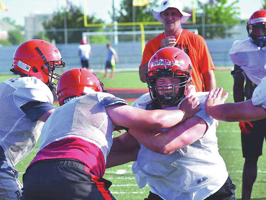 Edwardsville football coach Matt Martin, back, watches his linemen during a drill on Tuesday at the District 7 Sports Complex. Photo:       Matthew Kamp | For The Telegraph