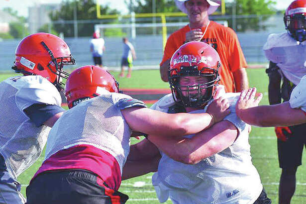 Edwardsville football coach Matt Martin, back, watches his linemen during a drill on Tuesday at the District 7 Sports Complex.