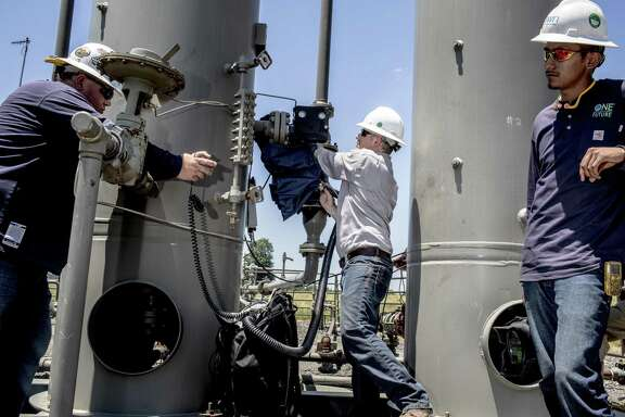 Southwestern Energy workers check on a suspected pipe leak at a well pad site in Damascus, Ark., June 28, 2016. The reputation of natural gas as a clean energy source in the fight against climate change rests in part on the abilities of workers tracking down and eliminating methane emissions.