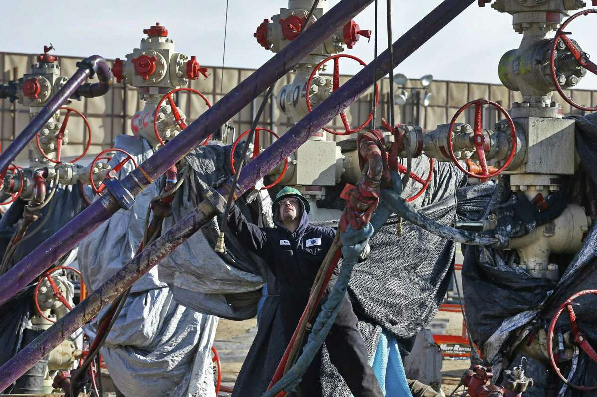 A worker adjusts pipes during a hydraulic fracturing operation at a well pad near Mead, Colorado. The reputation of natural gas as a clean energy source in the fight against climate change rests in part on reducing or eliminating methane emissions.