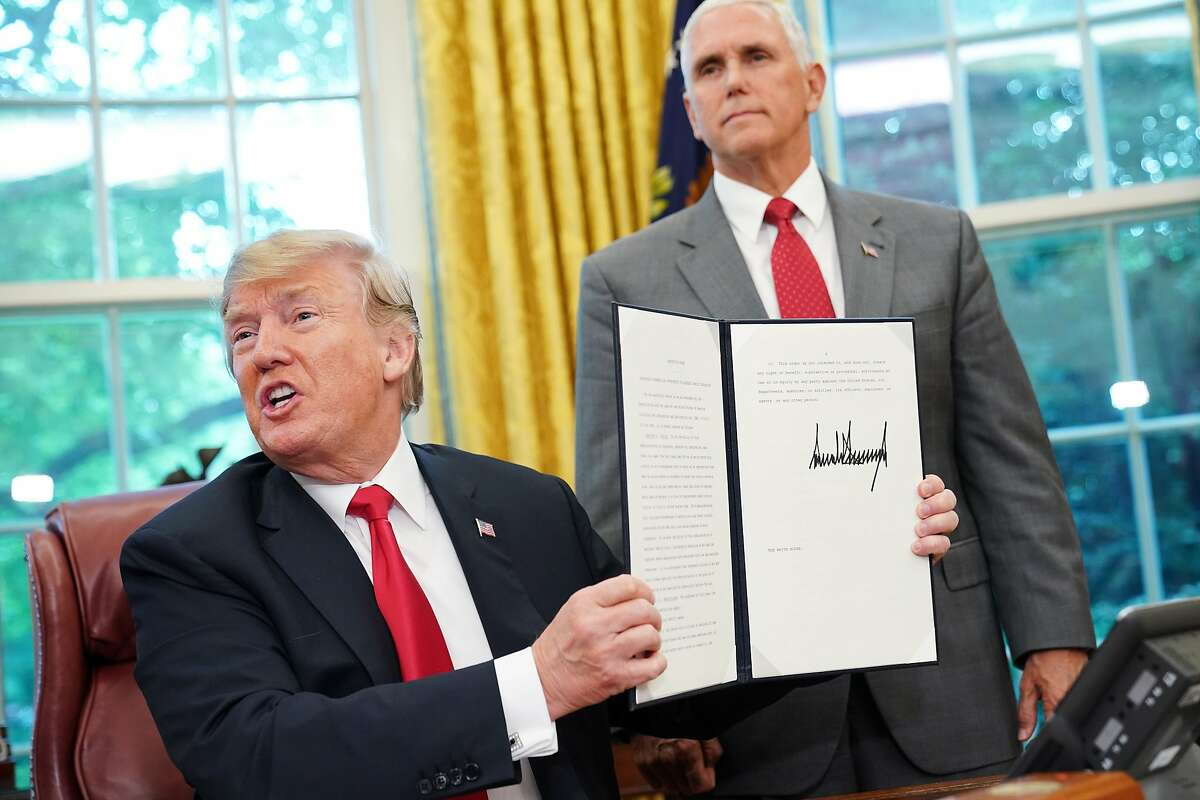 """Watched by Vice President Mike Pence, US President Donald Trump shows an executive order on immigration which he just signed in the Oval Office of the White House on June 20, 2018 in Washington, DC. US President Donald Trump on Wednesday signed an executive order aimed at putting an end to the controversial separation of migrant families at the border, reversing a harsh practice that had earned international scorn.""""It's about keeping families together,"""" Trump said at the signing ceremony. """"I did not like the sight of families being separated,"""" he added."""