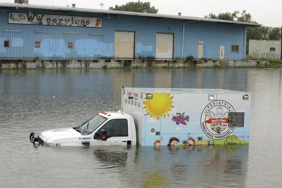 An ambulance sit stalled along the frontage road next to Expressway 83 as heavy rains caused water to rise and flood whole neighborhoods on Wednesday, June 20, 2018, in Weslaco, Texas. (Joel Martinez/The Monitor via AP)