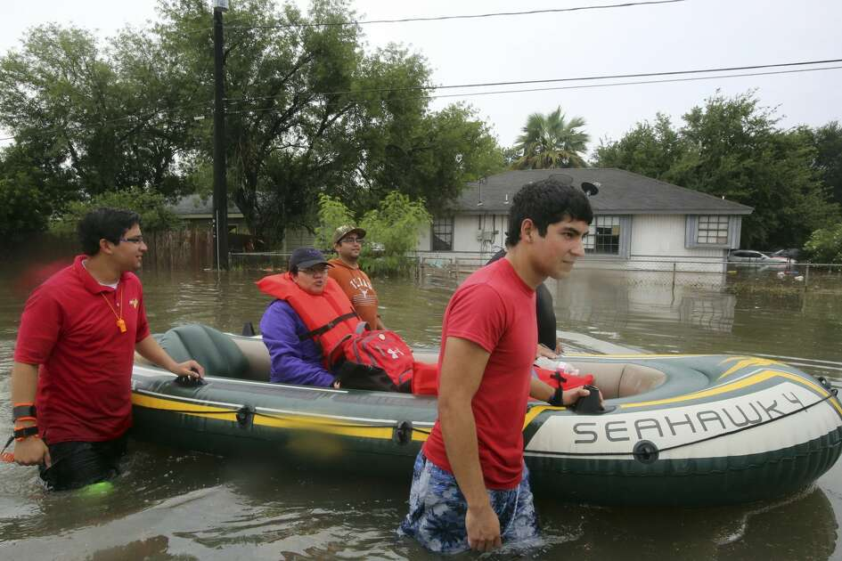 Volunteers use a raft to rescue residents from their homes as their move along the Frontage Road near Texas Boulevard after heavy rains caused water to rise and flood whole neighborhoods on Wednesday, June 20, 2018, in Weslaco, Texas.  (Joel Martinez/The Monitor via AP)