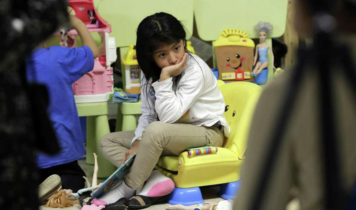 An immigrant child from Guatemala sits on a toy chair as she waits with her family at the Catholic Charities RGV, Thursday, June 21, 2018, in McAllen, Texas. Families that are processed and released by U.S. Customs and Border Protection get assistance and help with travel at the facility. (AP Photo/David J. Phillip)
