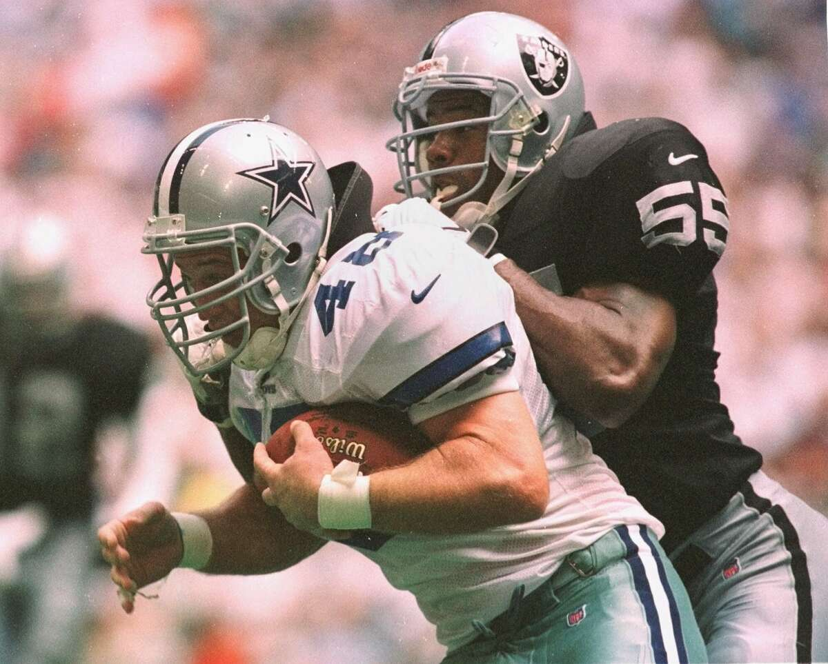 Oakland Raiders linebacker James Folston (55) brings down Dallas Cowboys fullback Daryl Johnston during the second quarter in Irving, Texas, Sunday afternoon, Sept. 27, 1998. (AP Photo/Frederic Larson)