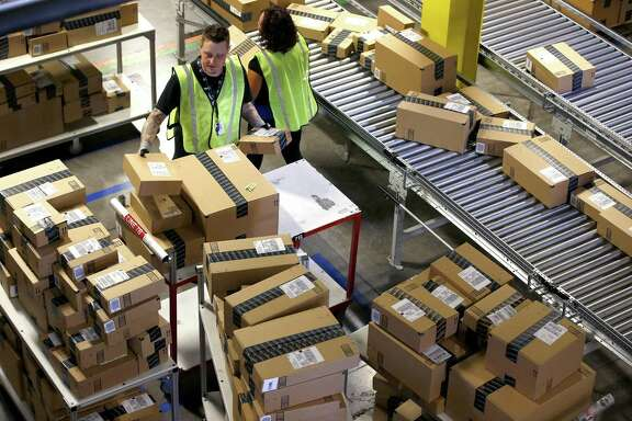 In this Dec. 2, 2013 file photo, Amazon.com employees organize outbound packages at an Amazon.com Fulfillment Center. The U.S. Supreme Court's latest ruling regarding online sales taxes means you'll be paying more for most items sold online.