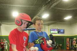 NASA East Major All-Stars Jack Hammock (left) and Reece Rothermel gather up baseballs after taking cuts in the 3K batting cages Wednesday night.